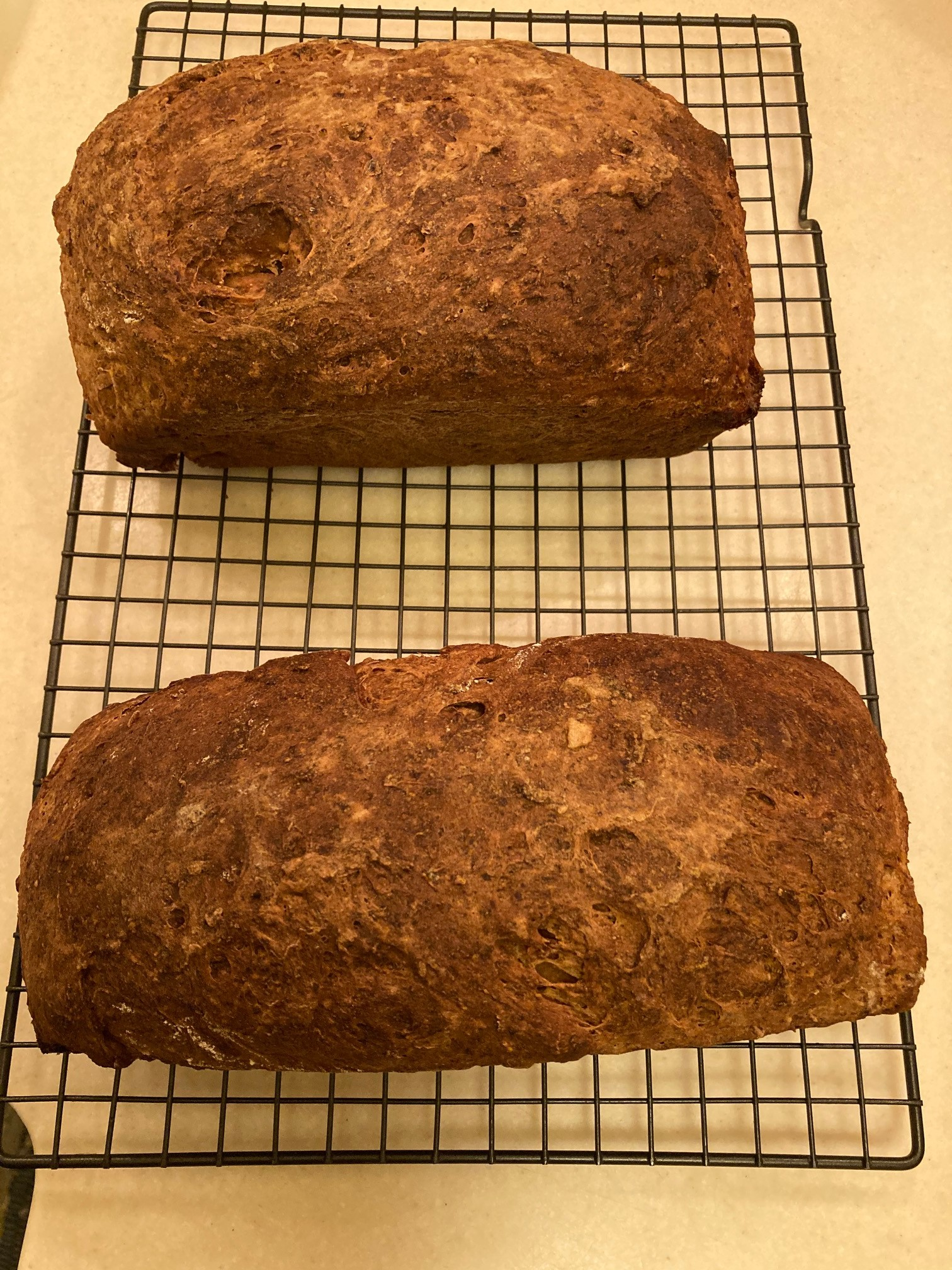 Two loaves of bread sit on a wire cooling rack.